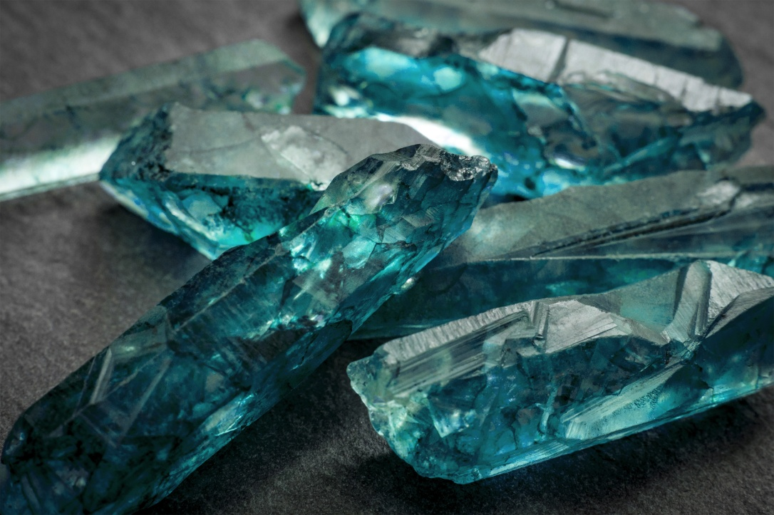 Aquamarines  and raw crystal gems concept with closeup of a bunch of blue uncut aquamarine, topaz or tourmaline crystals